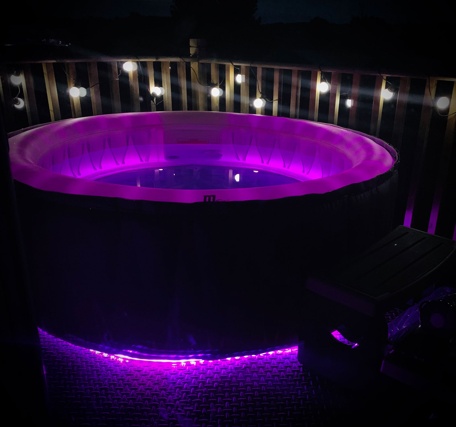 Deluxe hot tub at night with purple light