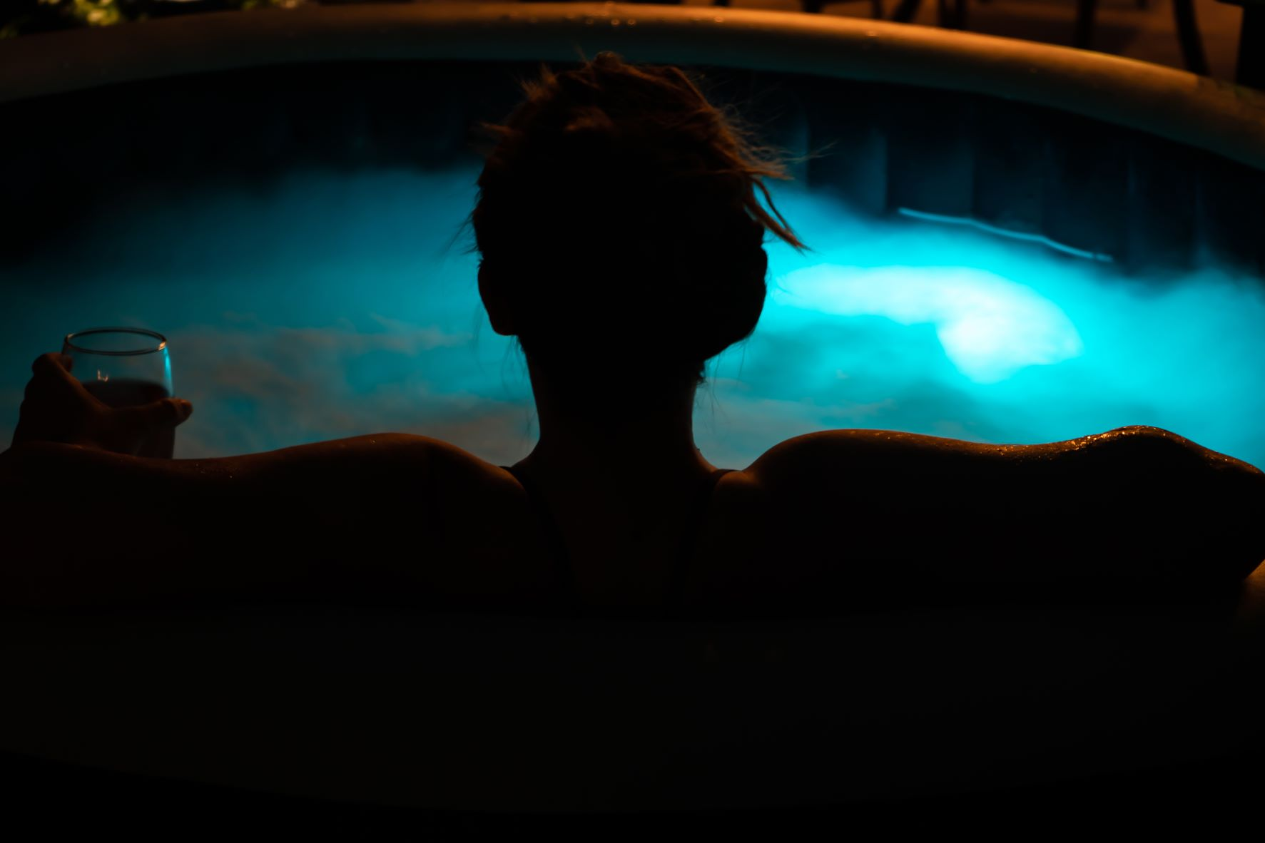 women relaxing in hot tub at night